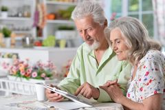 Senior couple using tablet. Happy senior couple using digital tablet in kitchen Royalty Free Stock Photos