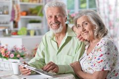 Senior couple using tablet. Happy senior couple using digital tablet in kitchen Royalty Free Stock Photography