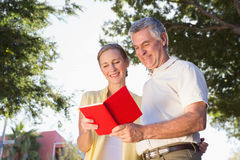 Happy senior couple using the guidebook Royalty Free Stock Photography