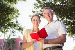 Happy senior couple using the guidebook Stock Photos