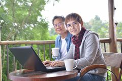 Happy senior couple using laptop computer at home. With green garden background Royalty Free Stock Photo