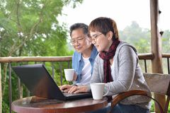 Happy senior couple using laptop computer at home. With green garden background Stock Images