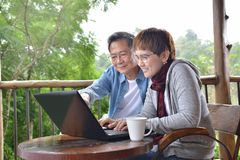 Happy senior couple using laptop computer at home. With green garden background Royalty Free Stock Images
