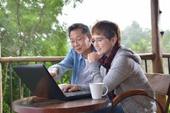 Happy senior couple using laptop computer at home. With green garden background Royalty Free Stock Image