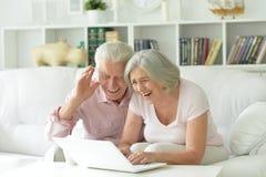 Happy senior couple using  laptop Stock Images