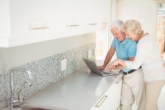 Happy senior couple using laptop in kitchen Stock Images