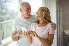 Happy senior couple using mobile phone in balcony. At home Stock Photo