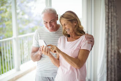 Happy senior couple using mobile phone in balcony. At home Royalty Free Stock Images