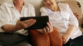 Happy senior couple using modern tablete stock video footage