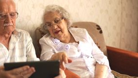 Happy senior couple using modern tablete stock video