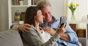 Happy senior couple using smartphone on couch royalty free stock photos