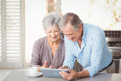 Happy senior couple using tablet Stock Images