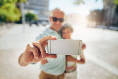 Happy senior couple on vacation taking a selfie Stock Image