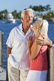 Happy Senior Couple On Vacation By Tropical Sea. Happy senior man and woman couple together on vacation by the sea in a tropical setting with bright clear blue Royalty Free Stock Photo