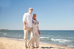 Happy senior couple walking along summer beach Royalty Free Stock Images