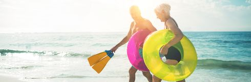 Happy senior couple walking on beach. With inflatable rings and flippers during sunny day Stock Photography