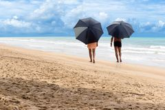 Happy senior couple walking on the beach with umbrella. Retirement concept Stock Photography