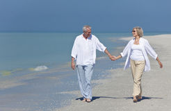 Happy Senior Couple Walking Holding Hands on Beach Stock Image