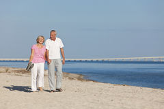 Happy Senior Couple Walking Holding Hands on Beach Royalty Free Stock Images