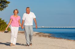 Happy Senior Couple Walking Holding Hands on a Beach. Happy senior man and woman couple walking laughing holding hands on vacation on a deserted tropical beach royalty free stock images