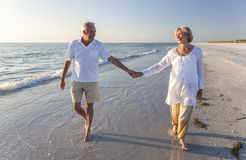 Happy Senior Couple Walking Holding Hands Tropical Beach. Happy senior men and women couple walking and holding hands on a deserted tropical beach with bright Stock Photo