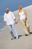 Happy Senior Couple Walking Holding Hands Tropical Beach. Happy senior men and women couple walking and holding hands on a deserted tropical beach with bright Royalty Free Stock Image