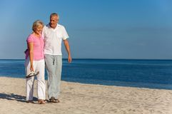 Happy Senior Couple Walking Laughing on a Beach royalty free stock photo