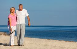 Happy Senior Couple Walking Laughing on a Beach stock photography