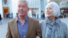 Happy Senior Couple Walking Through Outdoor Shopping Area stock video footage