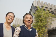Happy senior couple walking outdoors by traditional building in Beijing Stock Photography