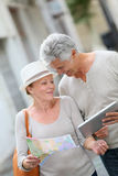 Happy senior couple walking in the streets with tablet Royalty Free Stock Photo