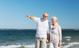 Happy senior couple walking on summer beach Stock Photos