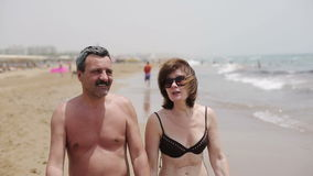 Happy senior couple walking together on a beach.  stock footage