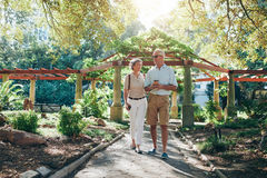 Happy senior couple walking together in a city park Stock Photography