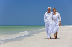 Happy Senior Couple Walking on A Tropical Beach. Romantic happy senior man and woman couple walking on a deserted tropical beach with bright clear blue sky