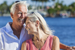 Happy Senior Couple Walking Tropical Sea or River. Happy romantic senior men and women romantic couple together embracing by tropical sea or river Royalty Free Stock Image