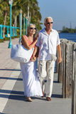 Happy Senior Couple Walking Tropical Sea or River. Happy senior men and women romantic couple walking together, holding hands & looking out to tropical sea or Royalty Free Stock Images