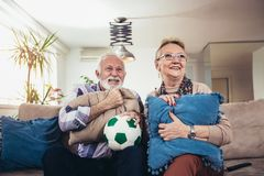 Happy senior couple watching soccer on tv and celebrating victory royalty free stock image