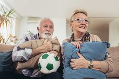 Happy senior couple watching soccer on tv. And celebrating victory at home Royalty Free Stock Images