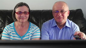 Happy senior couple watching television together stock video