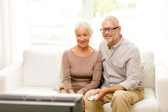 Happy senior couple watching tv at home. Family, technology, age and people concept - happy senior couple watching tv at home Royalty Free Stock Images