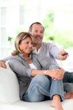 Happy senior couple watching tv Stock Photos