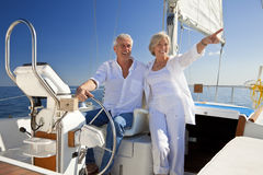Happy Senior Couple At The Wheel of a Sail Boat. A happy senior couple sitting at the wheel of a sail boat on a calm blue sea Stock Image