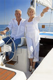 Happy Senior Couple At The Wheel of a Sail Boat Stock Image