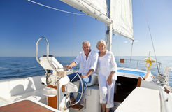 Happy Senior Couple At The Wheel of a Sail Boat. A happy senior couple sitting at the wheel of a sail boat on a calm blue sea Stock Images