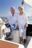 Happy Senior Couple At The Wheel of a Sail Boat. A happy senior couple sitting at the wheel of a sail boat on a calm blue sea Royalty Free Stock Photos