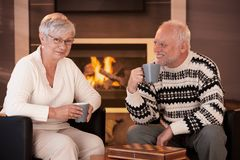 Happy senior couple on winter night at home. Sitting in front of fireplace in cosy living room, having tea Stock Image