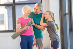 Happy senior couple with yoga mat and cute girl standing togethe Royalty Free Stock Photography