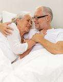 Happy senior coupler lying in bad at home Stock Photography