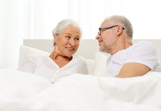 Happy senior coupler lying in bad at home Stock Image